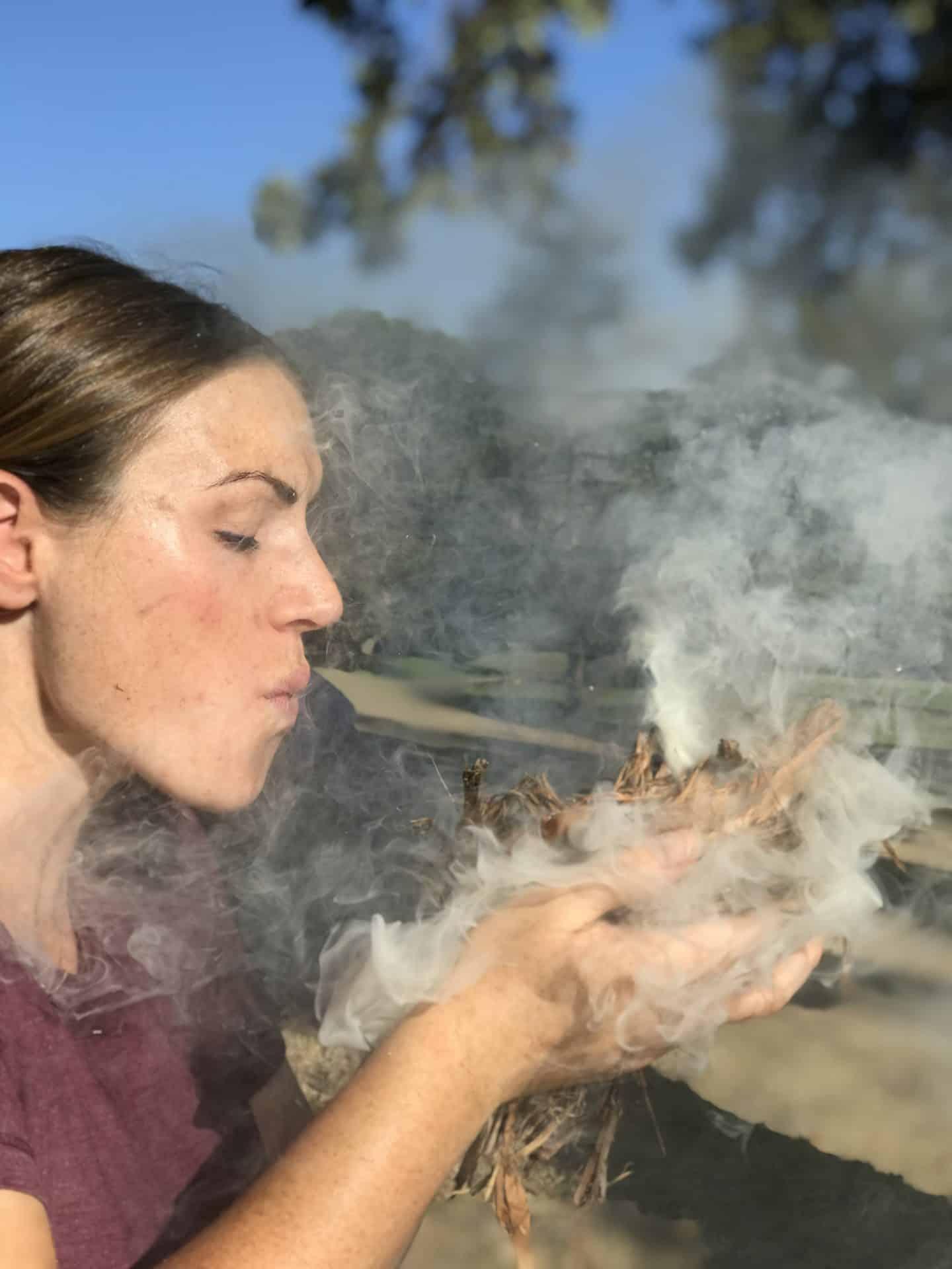 Survivalist blows on smoking brush