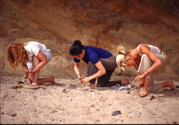 Survivalists in sand with sticks.